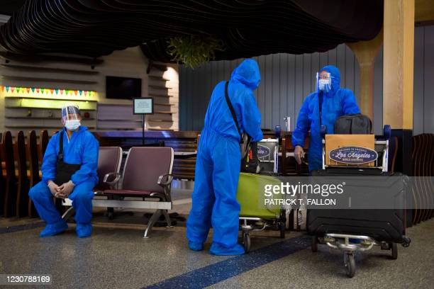 Maritime crew members arriving from the Philippines wear personal protective equipment on the arrivals level inside the Tom Bradley International...