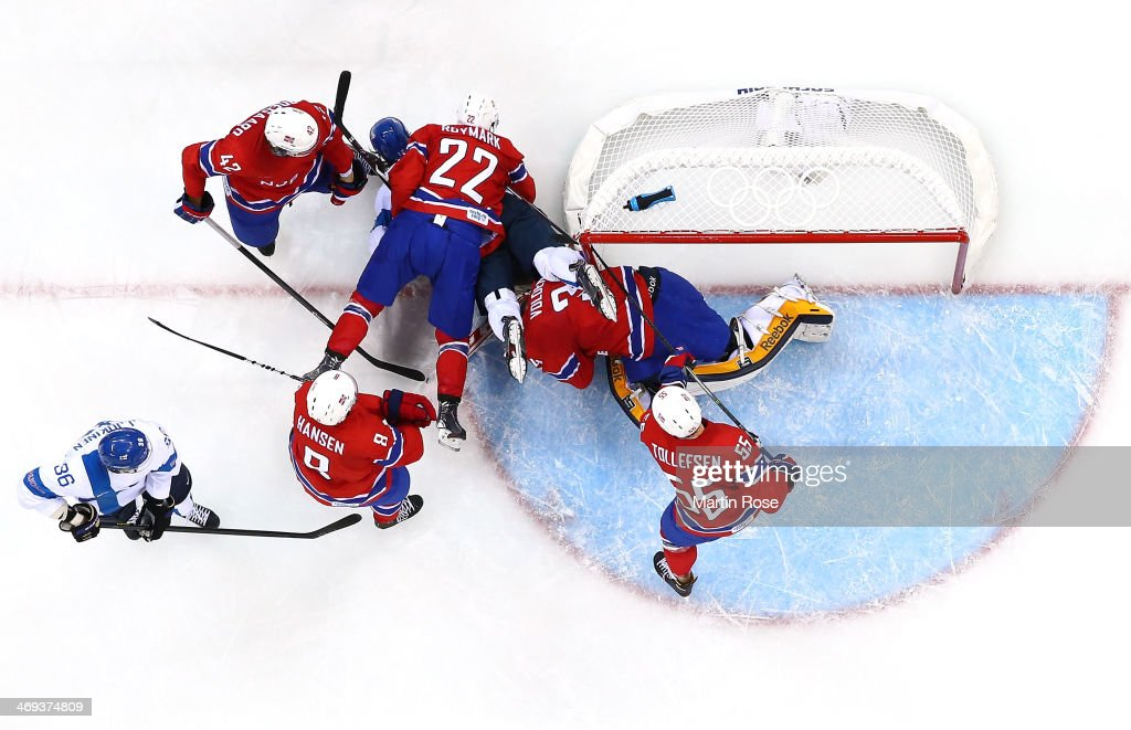 Maritn Roeymark #22 of Norway and Olli Jokinen #12 of Finland fall over Lars Volden #34 of Norway in the second period during the Men's Ice Hockey Preliminary Round Group B game on day seven of the Sochi 2014 Winter Olympics at Shayba Arena on February 14, 2014 in Sochi, Russia.