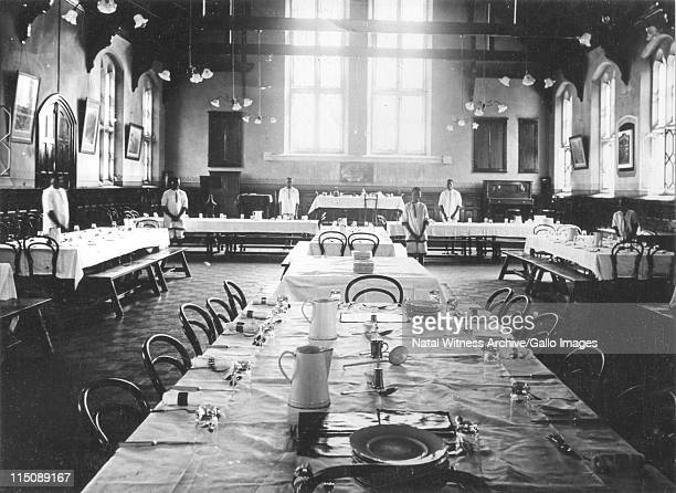 Maritzburg College. The Victoria Hall ready for the midday meal. Electric lamps replace the paraffin lamps and chairs are used together with benches.