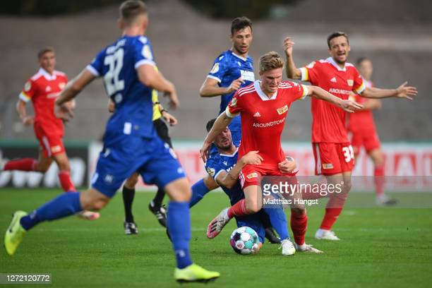 Marius Buelter of Berlin is challenged by Jerome Gondorf of Karlsruhe during the DFB Cup first round match between Karlsruher SC and 1. FC Union...