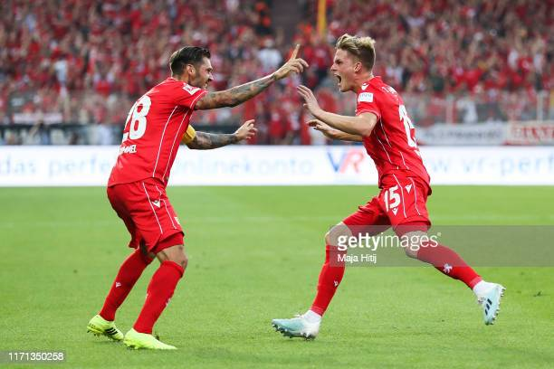 Marius Bulter celebrates with his team mate Christopher Trimmel of FC Union Berlin after scoring his team's first goal during the Bundesliga match...