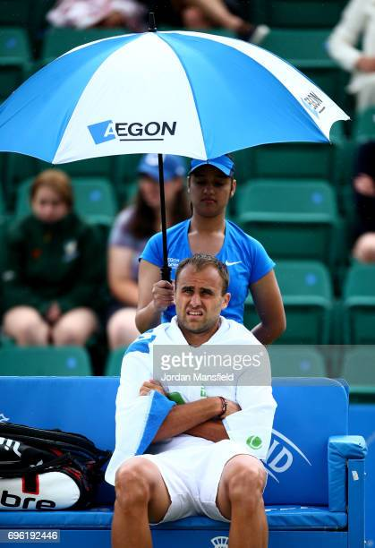 Marius Copil of Romania shelters under an umbrella as rain delay play during his Men's second round match against Reilly Opelka of the USA during day...