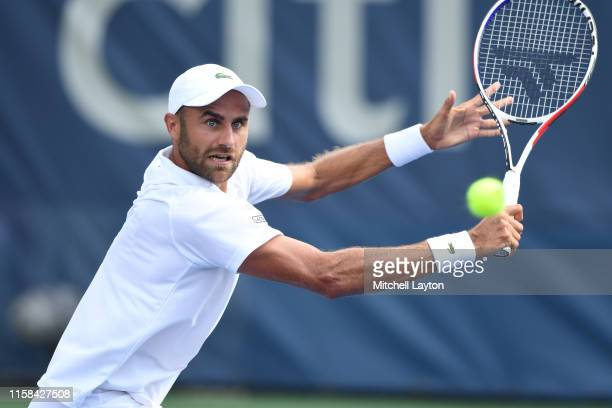 Marius Copil of the Romania returns a shot from Mikael Torpegaard of the Denmark during Day 1 of the Citi Open at Rock Creek Tennis Center on July...