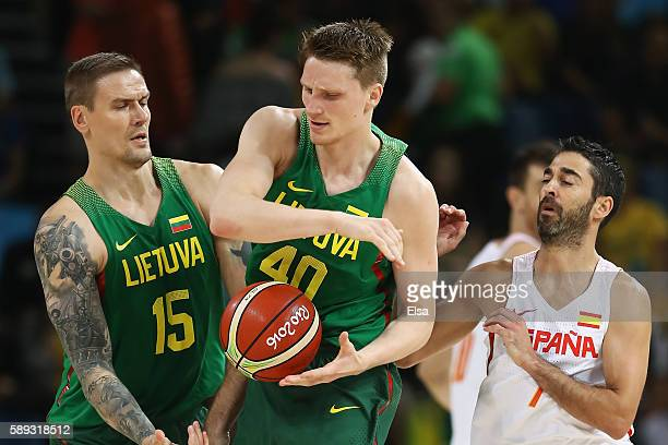 Marius Grigonis of Lithuania controls the ball against JuanCarlos Navarro of Spain as Robertas Javtokas of Lithuania looks on during the Men's...