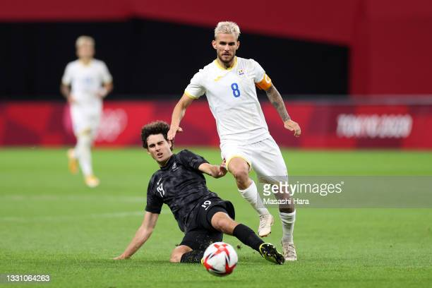 Marius Marin of Team Romania is challenged by Matthew Garbett of Team New Zealand during the Men's First Round Group B match between Romania and New...