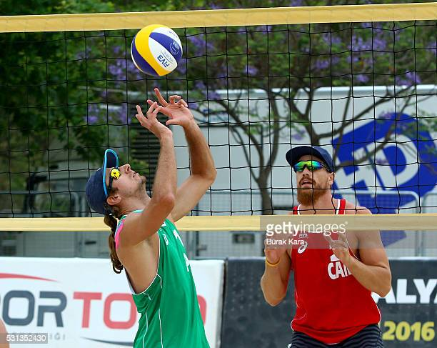 Marius Prudel of Poland sets the Mikasa as Sam Pedlow of Canada watches him during the 5th day of the FIVB Antalya Open beach volley tournament May...