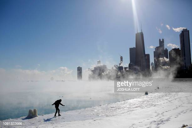 TOPSHOT Marius Radoi keeps his balance as he walks on the edge of Lake Michigan's shore line as temperatures dropped to 20 degrees F on January 30...