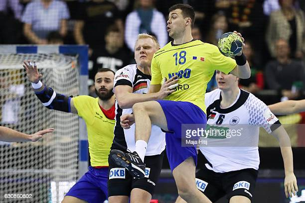 Marius Sadoveac of Romania is challenged by Patrick Wiencek of Germany during the International Handball Friendly match Germany v Romania on January...