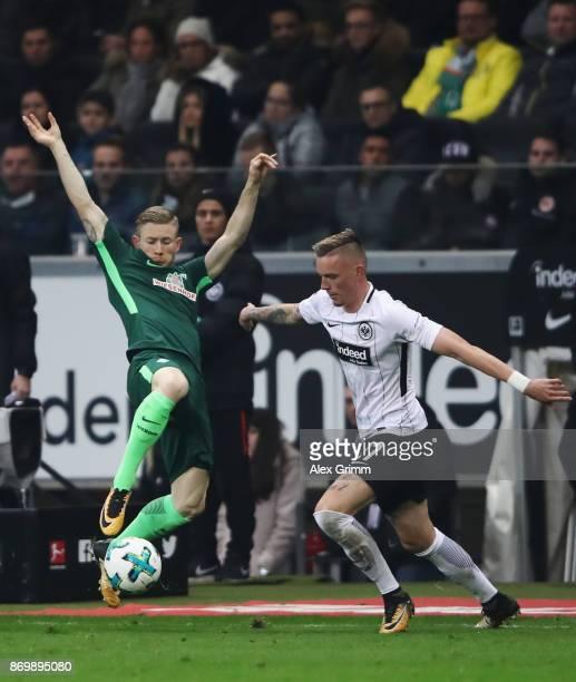 Marius Wolf of Frankfurt is challenged by Florian Kainz of Bremen during the Bundesliga match between Eintracht Frankfurt and SV Werder Bremen at...