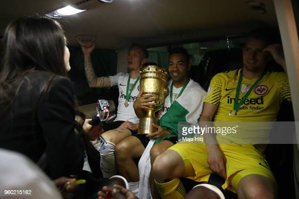 Marius Wolf of Frankfurt Marco Fabian of Frankfurt and Lukas Hradecky of Frankfurt sit in a care with the trophy after the DFB Cup final between...