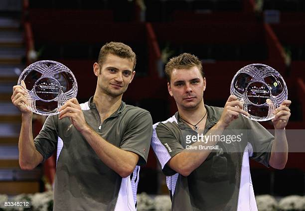 Mariusz Fyrstenberg and Marcin Matkowski of Poland hold aloft their trophies after a straight sets victory over Mark Knowles of the Bahamas and...