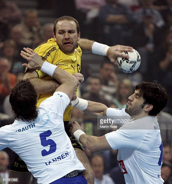Mariusz Jurasik of Kronau Oestringen is attacked by Torsten Jansen and Bertrand Gille of Hamburg during the Handball DHB German Cup Final between HSV...