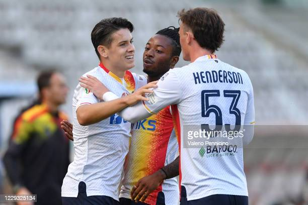 Mariusz Stepinski of US Lecce celebrates the opening goal with team mates Claud Adjapong and Liam Henderson during the Coppa Italia match between...