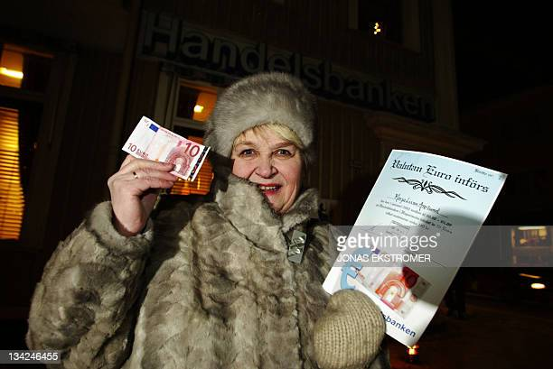 MarjaLiisa Asplund from Haparanda Sweden shows euro banknotes and an exchange certificate 01 January 2002 This northern Swedish town started using...