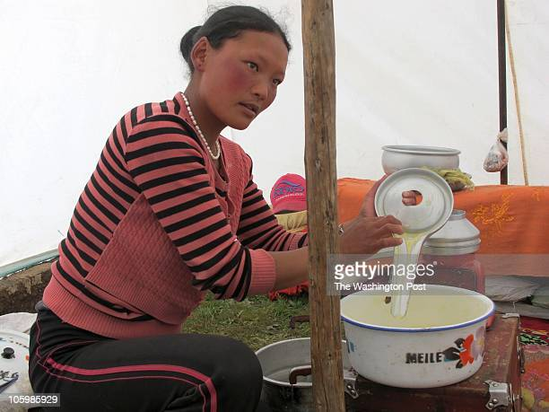Marjo Herji churns butter out of yak milk in her traditional tent in the Xiala grasslands Qinghai Province China in the southrn mountain grazing land...