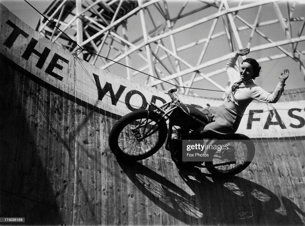 Marjorie Dare (Doris Smith) riding hands free around 'The Wall of Death' sideshow at the Kursaal amusement park in Southend, Essex, 1938.
