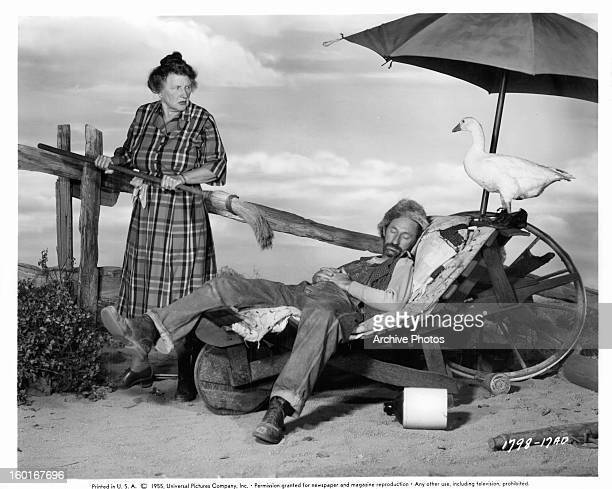 Marjorie Main holds a broom up to a sleeping Arthur Hunnicutt in a scene from the film 'The Kettles In The Ozarks' 1956