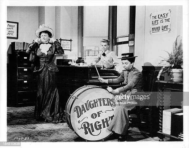 Marjorie Main plugs her ears while VeraEllen sits at a desk and Alice Pearce plays a giant drum in a scene from the film 'The Belle Of New York' 1952