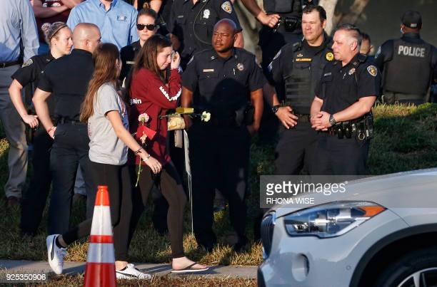 TOPSHOT Marjory Stoneman Douglas High School staff teachers and students return to school greeted by police and well wishers in Parkland Florida on...