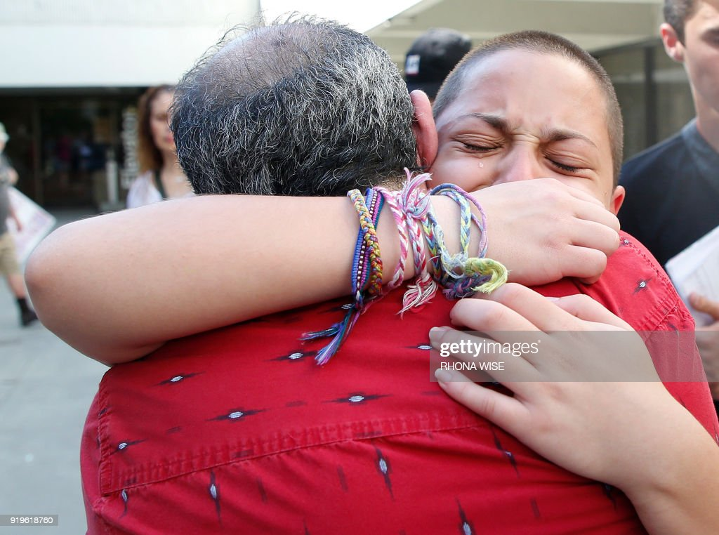 Marjory Stoneman Douglas High School student Emma Gonzalez hugs her father Jose after speaking at a rally for gun control at the Broward County Federal Courthouse in Fort Lauderdale, Florida on February 17, 2018. Seventeen perished and more than a dozen were wounded in the hail of bullets at Marjory Stoneman Douglas High School in Parkland,Florida the latest mass shooting to devastate a small US community and renew calls for gun control. /
