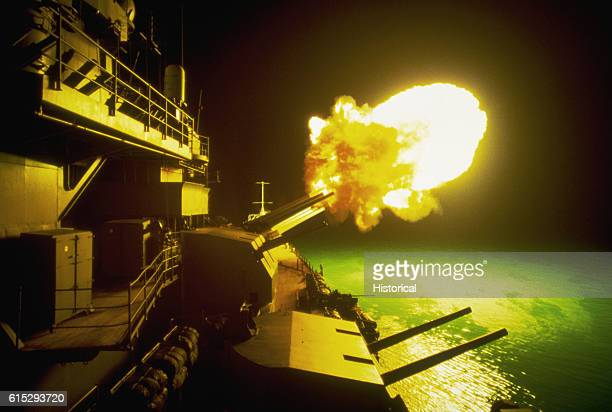 A Mark 7 16inch/50 caliber gun is fired aboard the battleship USS Missouri as night shelling of Iraqi targets takes place along the northern Kuwaiti...