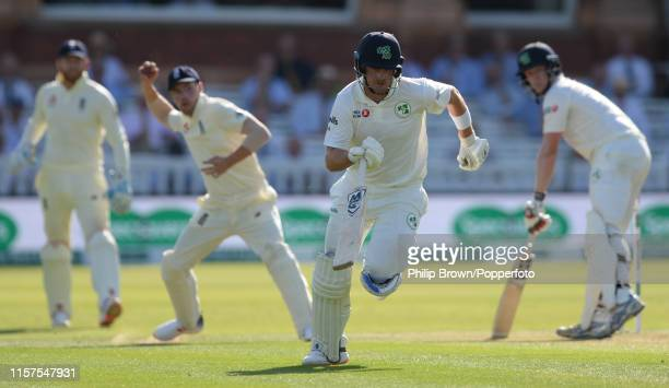 Mark Adair of Ireland runs as Rory Burns of England prepares to throw the ball during day one of the Specsavers Test Match between England and...