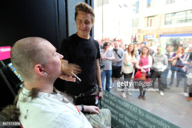 Mark Adams from Harlow in Essex has his head shaved in the window of HMV in Oxford Street London in aid of the Teenage Cancer Trust The charity event...