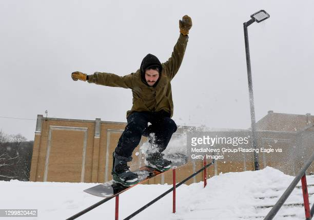 Mark Alexander, of Reading, snowboards on the hill and railing for the steps in front of the Reading High Geigle Complex in Reading. Monday morning...