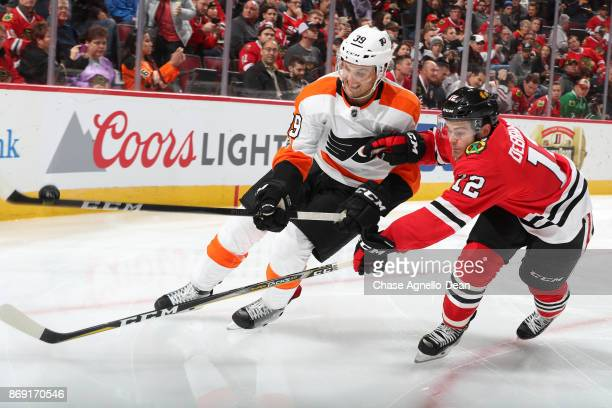 Mark Alt of the Philadelphia Flyers and Alex DeBrincat of the Chicago Blackhawks chase the puck in the second period at the United Center on November...