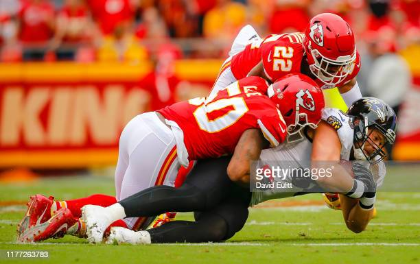 Mark Andrews of the Baltimore Ravens falls during the tackle of Juan Thornhill of the Kansas City Chiefs and Darron Lee of the Kansas City Chiefs at...