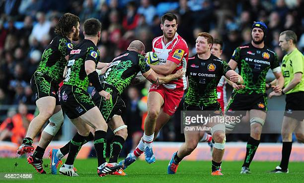 Mark Atkinson of Gloucester is tackled by James Scaysbrook and Sam Simmonds of Exeter Chiefs during the LV= Cup match between Exeter Chiefs and...