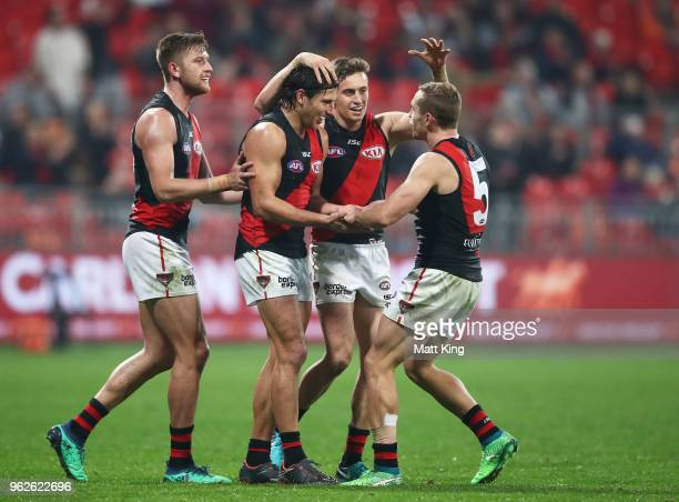 Mark Baguley of the Bombers celebrates with team mates after kicking a goal during the round 10 AFL match between the Greater Western Sydney Giants...
