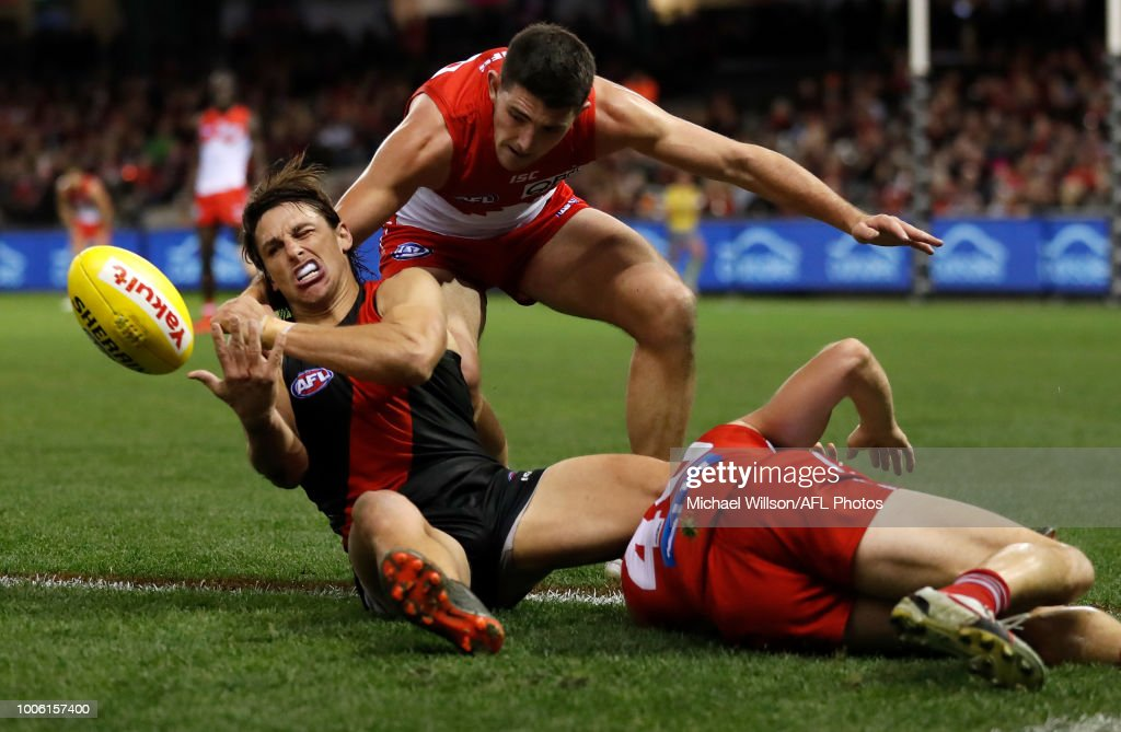 Mark Baguley of the Bombers is tackled by Colin O'Riordan of the Swans during the 2018 AFL round 19 match between the Essendon Bombers and the Sydney Swans at Etihad Stadium on July 27, 2018 in Melbourne, Australia.
