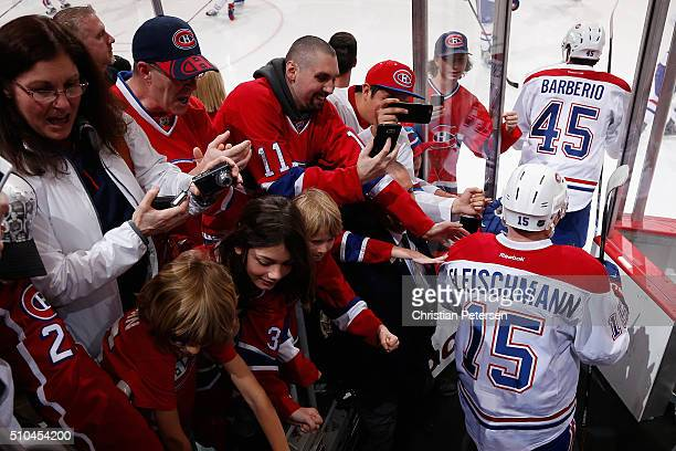 Mark Barberio and Tomas Fleischmann of the Montreal Canadiens walk past fans as they take the ice for warm ups to the NHL game against the Arizona...