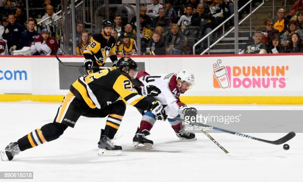 Mark Barberio of the Colorado Avalanche and Matt Hunwick of the Pittsburgh Penguins battle for a puck at PPG Paints Arena on December 11 2017 in...