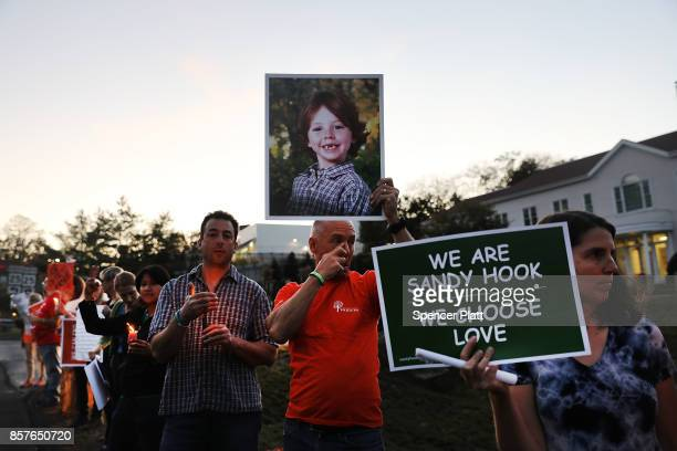 Mark Barden holds up a picture of his son Daniel who was killed in the Sandy Hook masracre during a vigil remembering the 59 people killed in...