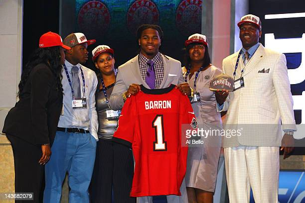 Mark Barron of Alabama holds up a jersey as he stands on stage and poses for a photo with his family after he was selected overall by the Tampa Bay...