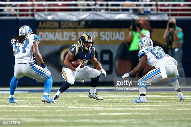 Mark Barron of the St. Louis Rams carries the ball as Josh Bynes and Tahir Whitehead of the Detroit Lions defend in the second quarter at the Edward...