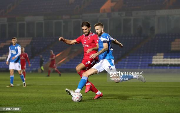 Mark Beevers of Peterborough United is challenged by Harry Cardwell of Chorley FC during the FA Cup Second Round match between Peterborough United...