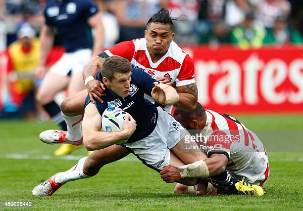 Mark Bennett of Scotland is hauled down by Male Sau and Michael Leitch of Japan during the 2015 Rugby World Cup Pool B match between Scotland and...