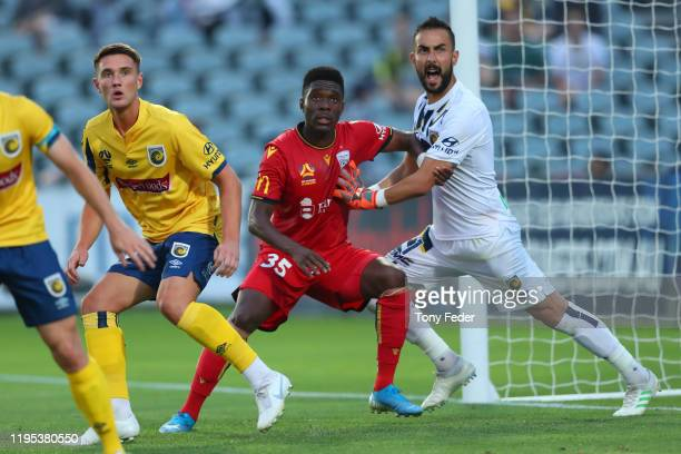 Mark Birighitti of the Central Coast Mariners and Al Hassan Toure of Adelaide United during the round 11 ALeague match between the Central Coast...