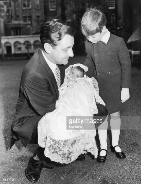 Mark Birley with his daughter India Jane after the baby's christening at Holy Trinity Brompton 11th April 1961 Watching them is the baby's older...