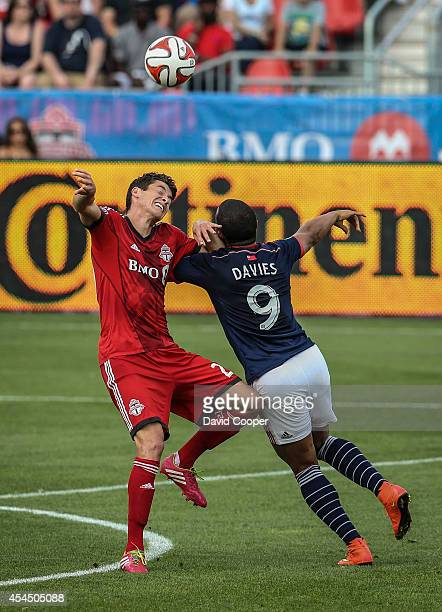 Mark Bloom of TFC goes airborne for the ball with Charlie Davies of the Revolution during the game between Toronto FC and New England Revolution