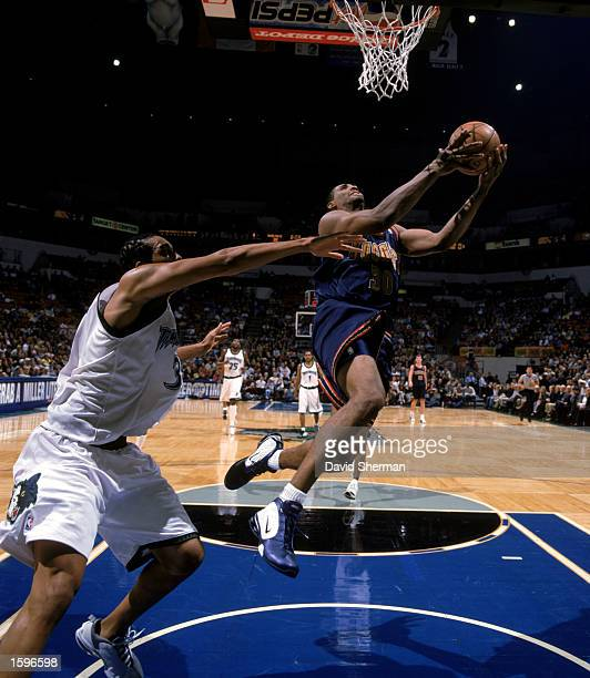 Mark Blount of the Denver Nuggets gets possession under the basket against the defense of Loren Woods of the Minnesota Timberwolves during the NBA...