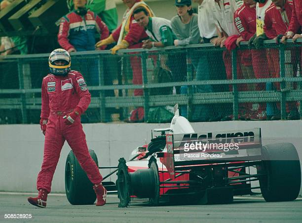 Mark Blundell of Great Britain, driver of the Marlboro McLaren Mercedes McLaren MP4/10B Mercedes V10 walks back in the pits after a last lap puncture...
