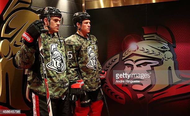 Mark Borowiecki and Chris Neil of the Ottawa Senators stand outside the lockeroom wearing camouflage jerseys prior to a game against the Winnipeg...