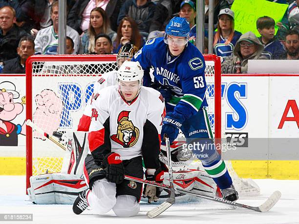 Mark Borowiecki of the Ottawa Senators and Bo Horvat of the Vancouver Canucks eye the puck in front of Craig Anderson of the Senators during their...