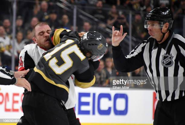 Mark Borowiecki of the Ottawa Senators and Jon Merrill of the Vegas Golden Knights fight as linesman Pierre Racicot moves in during the first period...