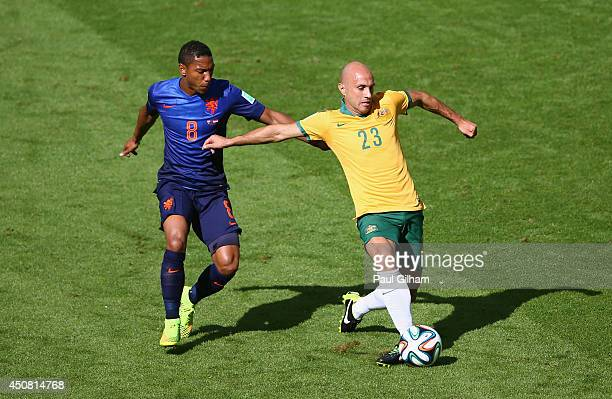 Mark Bresciano of Australia controls the ball as Jonathan de Guzman of the Netherlands give chase during the 2014 FIFA World Cup Brazil Group B match...