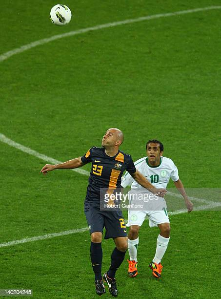 Mark Bresciano of Australia heads the ball ahead of Mohammed Bandar Alshehri of Saudi Arabia during the Group D 2014 FIFA World Cup Asian Qualifier...